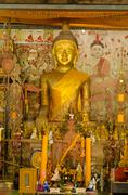 Stock Photo of Ancient golden Buddhas and mural mythology buddhist religion on wall