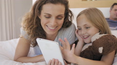 Mature mom and kid child in bed with tablet device Stock Footage