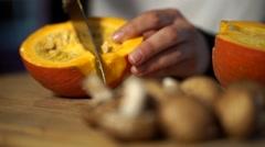 Cook cuttting a pumpkin Stock Footage