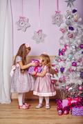 Sisters with gifts near Christmas tree. Stock Photos