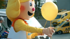 Happy mascot is giving away balloons to the children Stock Footage