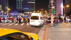 Ambulance car pass intersection, busy traffic junction at night time Stock Footage