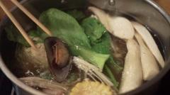 Put the raw food to sukiyaki Pot with hot water Stock Footage