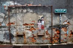 Street Mural tittle Children on the Swing painted by Louis Gan in Penang - stock photo