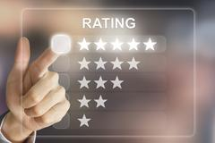 business hand pushing rating on virtual screen - stock photo