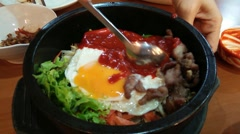 Mixing of bibimbap in heated stone bowl, korean dish Stock Footage