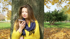 Woman leaning on tree in the autumnal park and talking on loudspeaker - stock footage