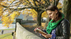 Woman standing on boulevard and reading a book Stock Footage