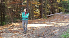 Woman relaxing in the autumnal forest and smiling to the camera Stock Footage