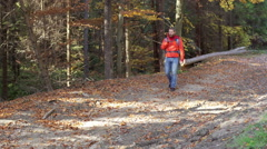 Man walking in the autumnal forest and chatting on loudspeaker - stock footage