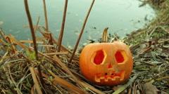 pumpkin next to lake jack o lantern - stock footage