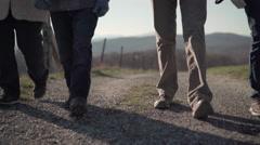 Feet of people walking on gravel path Stock Footage