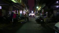 POV walk through dark Taipei street, few local people on way, dim illumination Stock Footage
