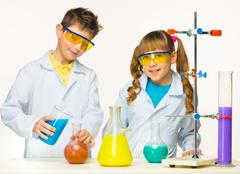 Two cute children at chemistry lesson making experiments Stock Photos