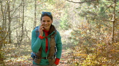 Woman walking in the autumnal forest and talking on cellphone, steadycam shot Stock Footage