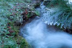 icicles on mountain river in winter - stock photo