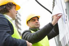 Engineer and constructor worker at construction site - stock photo