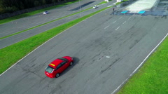 Red sports car is driving on a slippery track with water fountains Stock Footage
