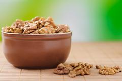 walnuts on bamboo table cloth - stock photo