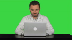 Stock Video Footage of Smiling male doctor sitting at table with laptop on a Green Screen, Chroma Key