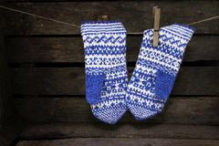 Jacquard mittens hanging on a rope - stock photo