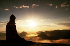 Stock Photo of Beautiful  young woman tourist enjoy daybreak on the sharp corner of sandston