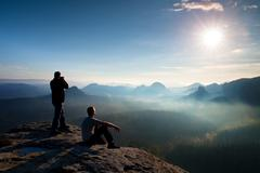 Hiker and photo enthusiast stay with tripod on cliff and thinking. Dreamy fog - stock photo