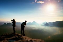 Hiker and photo enthusiast stay on cliff and thinking. Dreamy fogy landscape, - stock photo