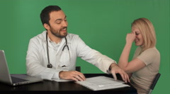 Smiling doctor read medical history of young woman at hospital on a Green Screen Stock Footage