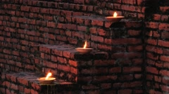 Candles burn at the stairs to the old Buddhist temple in Sukhithai, Thailand. Stock Footage