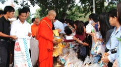 People bring food offerings to a Buddhist monk in Sukhothai, Thailand. - stock footage