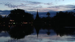 View to the temple reflected in the pond before sunrise in Sukhothai, Thailand. Stock Footage
