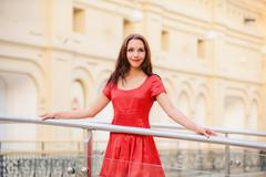 Woman in red dress about handrail - stock photo