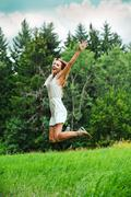 Fun happy young woman jumping up Stock Photos