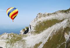 Hot air balloon crossing a mountain in the alps Stock Photos