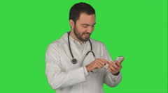 Happy doctor using his smartphone  on a Green Screen, Chroma Key - stock footage