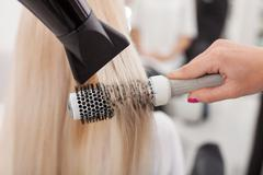 Professional female hairstylist is working with hair-drier - stock photo