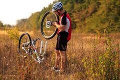 Man cyclist repairing a bike  against green nature - stock photo
