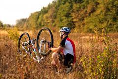 Man cyclist repairing a bike  against green nature Stock Photos