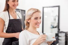 Beautiful blond girl is attending hairdressing saloon Stock Photos