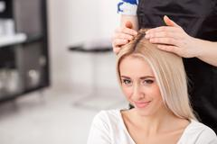 Cheerful blond girl is attending hairdressing salon - stock photo