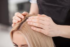Skillful female hairstylist is serving her client Stock Photos