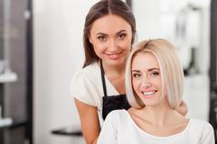 Beautiful blond girl is attending hairdressing saloon - stock photo