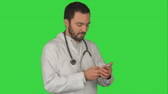 Doctor makes telephone call on a Green Screen, Chroma Key Stock Footage
