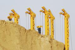 Construction site with drilling rigs behind a sand hill - stock photo