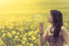 Beautiful woman blowing one soap bubble in yellow summer meadow - stock photo