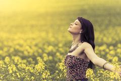 Happy woman in ocean of yellow flowers - stock photo