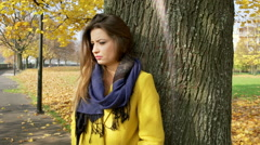 Morose woman leaning on tree in the park and thinking  Stock Footage