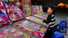 Little asian boy confused, playing gaming machine, pinball Stock Footage