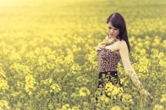 Beautiful woman in meadow of yellow flowers touching flower - stock photo